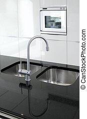Küche Wasserhahn und Backofen modern schwarz und weiß.