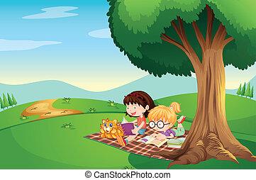 Kinder lesen unter dem Baum mit einer Katze.