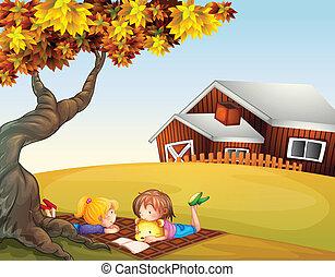 Kinder lesen unter einem großen Baum