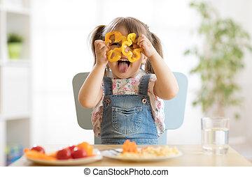 Kindermädchen hat Spaß mit Gemüse im Kinderzimmer.