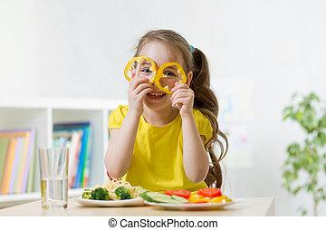 Kindermädchen hat Spaß mit Gemüse in der Küche.