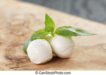 Kleine Eier Mozzarella mit Basilikumblättern.