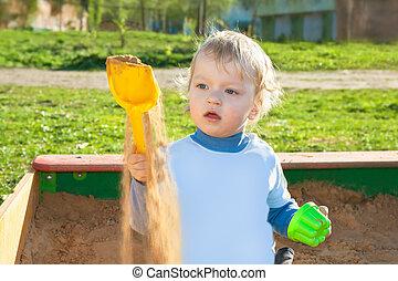 Kleine Kinder spielen in einem Sandkasten.