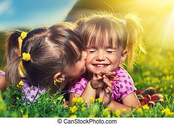 Kleine Mädchen küssen und lachen im Sommer draußen
