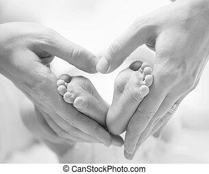 Kleine Neugeborene Füße auf weiblichen Herzen formten sich die Hände.
