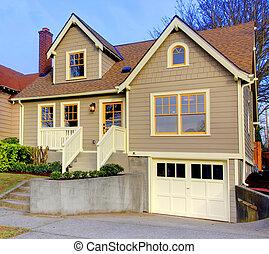 Kleines, neues braunes Haus mit orangen Türen und Fenstern.