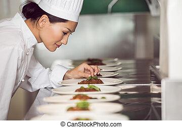 Konzentrierte Köchin, die in der Küche Essen macht.