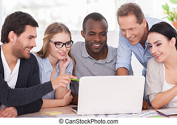 Kreatives Team arbeitet an Projekt. Eine Gruppe von Geschäftsleuten in zwangloser Kleidung sitzt zusammen am Tisch und schaut auf den Laptop