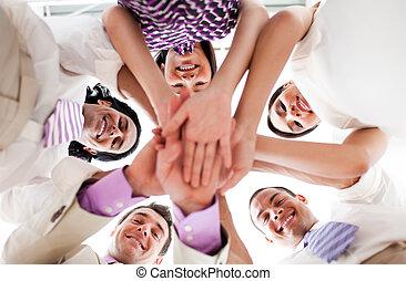 Lächelnde Geschäftsleute halten Händchen in einem Kreis