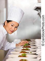 Lächelnde Köchin, die in der Küche Essen macht.