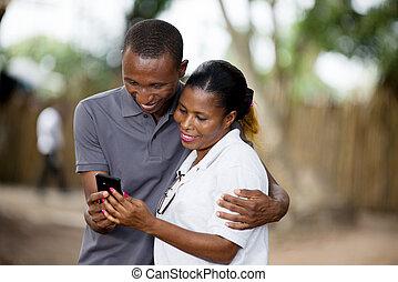 Lächelndes Paar mit Handy draußen.