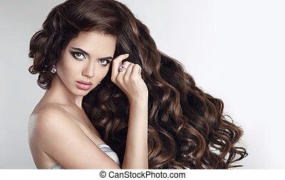 Lange Haare. Schöne Brunette-Mädchen-Porträt mit langem glänzendem, glänzenden Haarstyle. Wunderschönes Modell mit lockigen Haaren . Modeschmuckset.