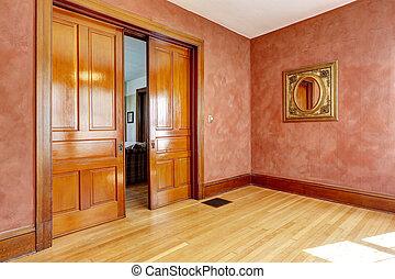 Leeres Zimmer in hellroter Farbe mit Schiebetür.