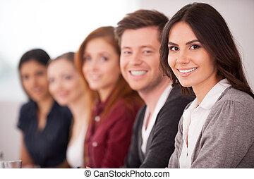 Leute im Seminar. Attraktive junge Frau lächelt vor der Kamera, während andere hinter ihr sitzen