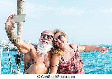 leute, paar, reise, segelboot, feiern, älter, -, glücklich, haben, smartphone, jubiläum, selfie, nehmen, beweglich, urlaub, lebensstil, begriff, beziehung, spaß, reise, wedding, liebe, fällig, boot