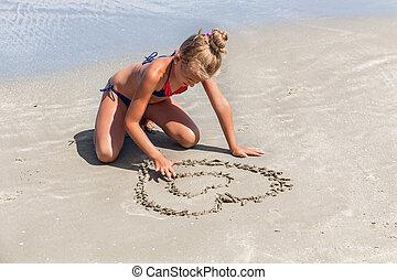 Liebe das Meer - kleine Mädchen, die Herzform im Sand.