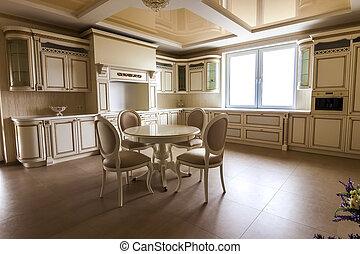 Luxus moderne Küchenausstattung. Küche in Luxushaus mit Beige-Schränke. Tisch und Stühle