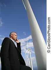 Mann mit Handy neben Windrädern