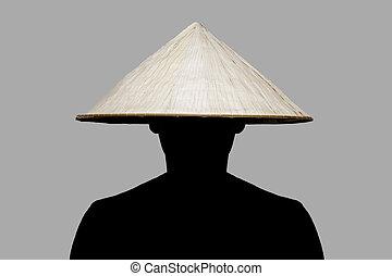 Mann mit traditionellem Hut aus Asien aus Weiden.