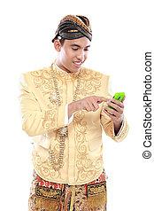 Mann mit traditionellem Java-Anzug mit Handy