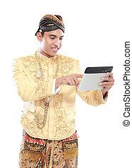 Mann mit traditionellem Java-Anzug mit Tablet PC