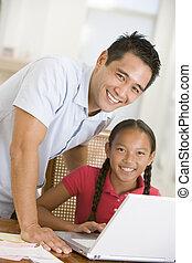 Mann und junges Mädchen mit Laptop im Esszimmer lächelnd