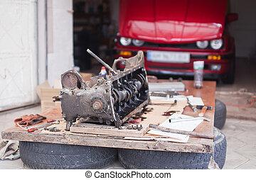 Maschinenreparatur, die auf dem Hintergrund eines roten Autos liegt.