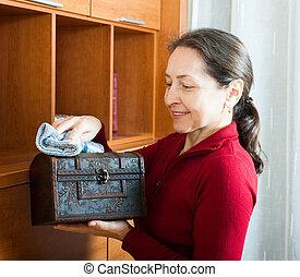Mature-Frau wischt Staub aus Holztruhe.