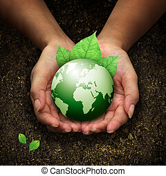 Menschenhände halten grüne Erde