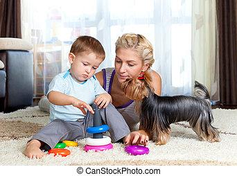 Mutter, Kind und Hund spielen drinnen.