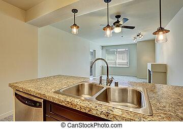 Nahaufnahme des doppelten Spülbeckens mit Granitplatte in moderner Wohnung.