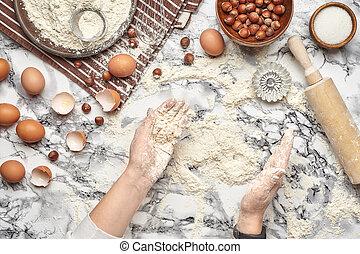 Nahaufnahme. Top Blick auf einen Bäckerkochplatz, die Hände arbeiten mit einem rohen Teig auf dem Marmortisch Hintergrund.