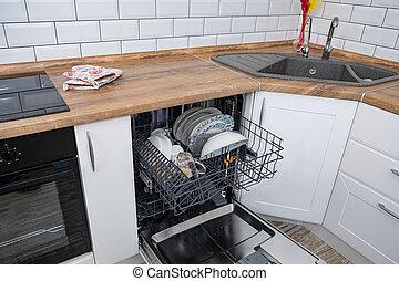 Offener Geschirrspüler mit schmutzigem Geschirr in der weißen Küche.