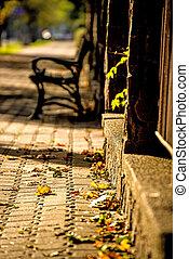 Parkbank in einer Stadt in der Herbstsonne.