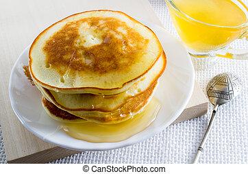 Pfannkuchen mit Honig auf dem weißen Teller.