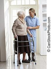 Pfleger, der älteren Frau beim Laufen hilft