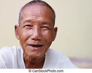 Portrait des glücklichen alten asiatischen Mannes, der vor der Kamera lächelt