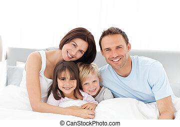 Portrait einer glücklichen Familie, die auf dem Bett sitzt
