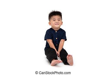 Portrait eines asiatischen Babyjungen, der auf dem Boden sitzt und schüchtern und lächelnd auf einem weißen Hintergrund, 1 Jahr 10 Monate alt