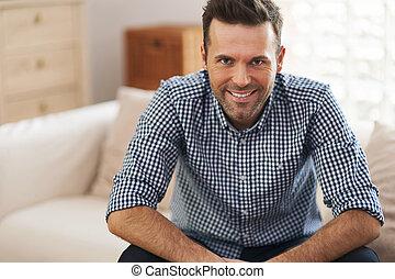 Portrait eines hübschen Mannes im Wohnzimmer.