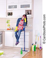 Putzfrau ruht sich auf dem Küchentisch aus