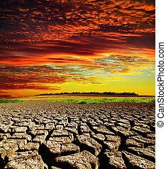 Roter, dramatischer Sonnenuntergang über der Erde