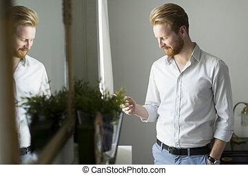 Rothaariger Mann mit Telefon im Zimmer.