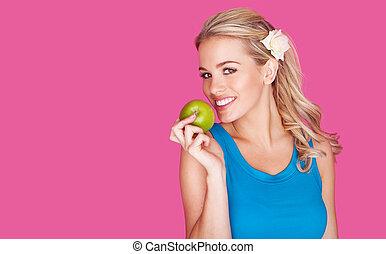Schöne gesunde junge Frau mit einem Apfel.