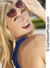 Schöne lachende blonde Frau in Herzform mit Sonnenbrille