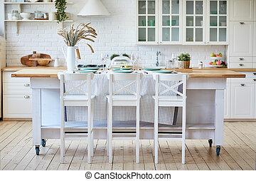 Schöne weiße Holzküche mit Inseltisch und Stühlen.