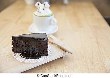 Schokoladenkuchen und grüner Tee mit Milchschaum auf der Tasse heißen grünen Tee.