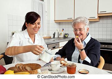 Schwester hilft älteren Frauen beim Frühstück