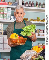 Senior Verkäufer verkauft Gemüse im Laden