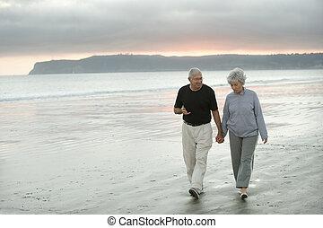 Senioren gehen am Strand spazieren